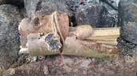 Split Cedar Bundled in Birch Bark left for next camper, Adirondack tradition. Added carved skull for fun.